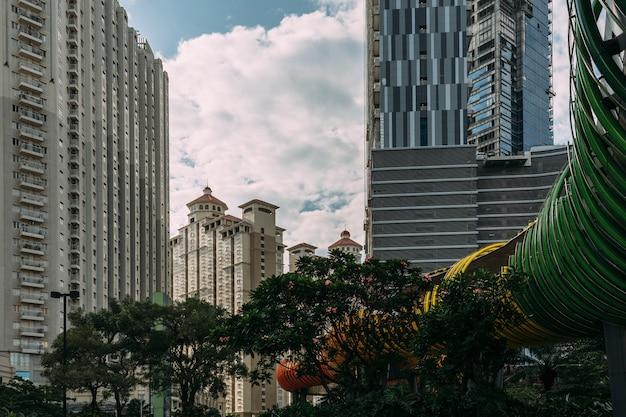 Zentrales stadtbild von jakarta mit hochhaus, wolkenkratzern und hotel im touristischen bereich mit grünen bäumen. Premium Fotos