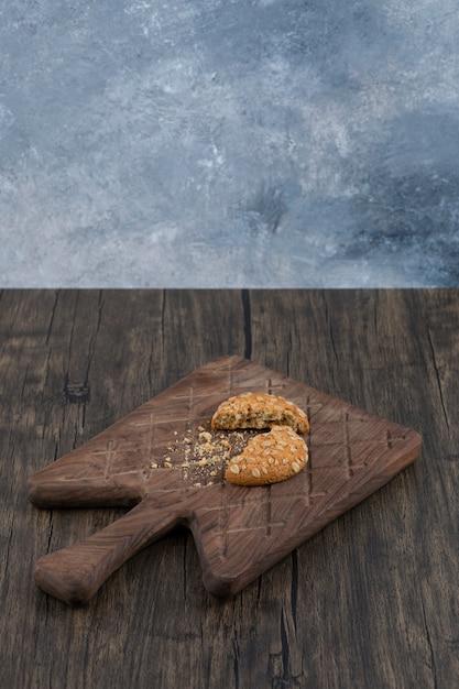 Zerbrochener köstlicher keks mit müsli auf einem hölzernen schneidebrett. Kostenlose Fotos