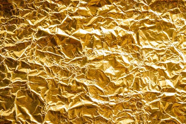 Zerknitterter goldfolien-beschaffenheitshintergrund Premium Fotos