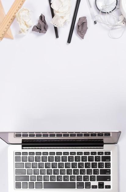 Zerknittertes papier mit büroartikel und einem offenen laptop auf weißem hintergrund Kostenlose Fotos