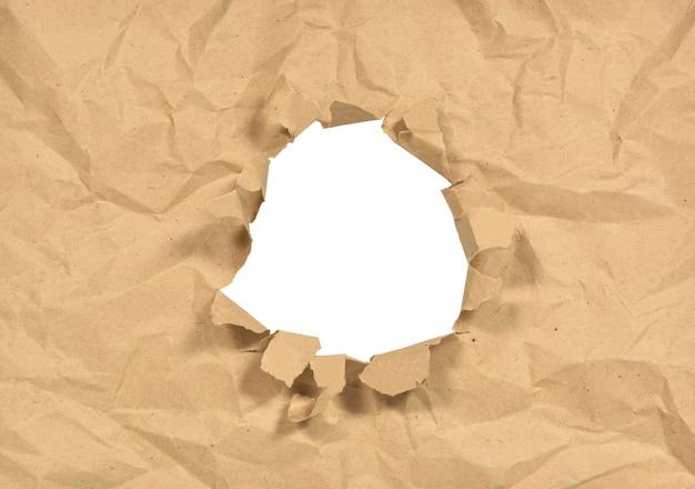 Zerknittertes papier mit einem loch in der mitte Premium Fotos
