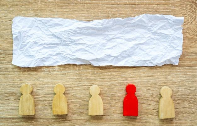 Zerknittertes papier und rote figur unter holzfiguren Premium Fotos