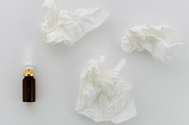 Zerknittertes weißbuch und tropfflasche auf weißem hintergrund Kostenlose Fotos