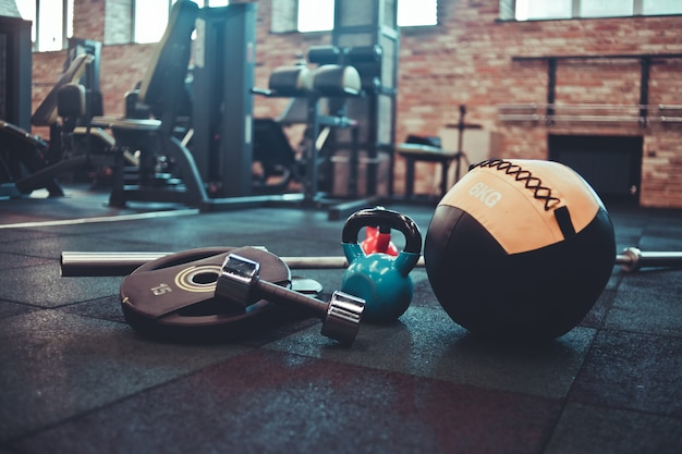 Zerlegte langhantel, medizinball, kettlebell, hantel auf dem boden im fitnessstudio liegend. sportgeräte für das training mit freiem gewicht. funktionstraining Premium Fotos