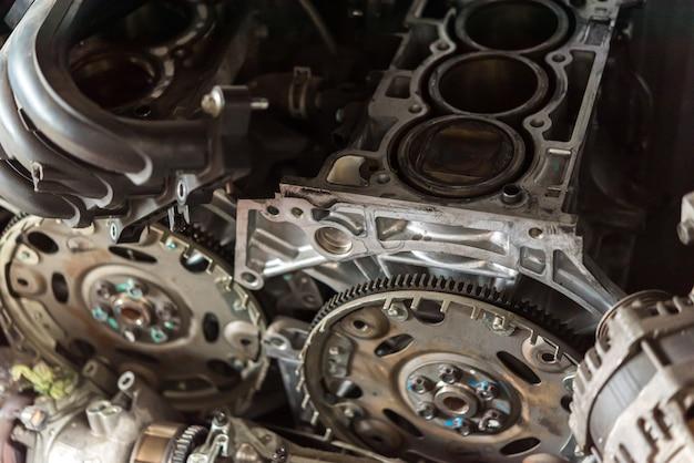 Zerlegter schmutziger motor und riemenscheibe des autos an der garage Premium Fotos