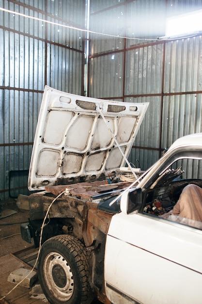 Zerlegtes weißes altes auto in der garage Premium Fotos