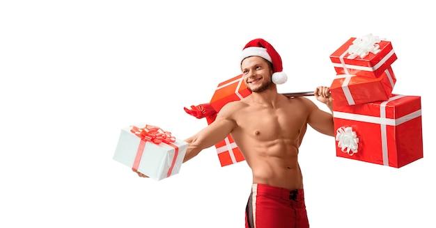 Zerrissener weihnachtsmann, der barbell hält und geschenke gibt Premium Fotos