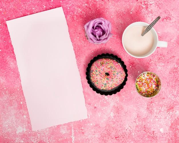 Zerrissenes leeres weißes papier mit streuseln; krapfen; rose und milch gegen rosa strukturierten hintergrund Kostenlose Fotos