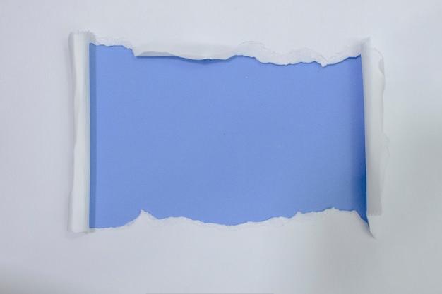 Zerrissenes weißbuch über blauem farbhintergrund Premium Fotos