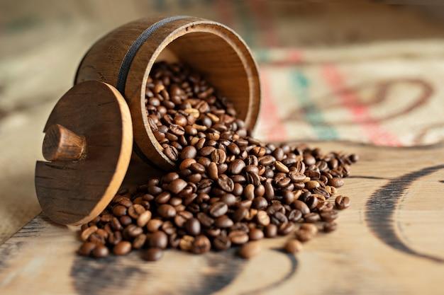 Zerstreute kaffeebohnen auf einem hölzernen brett. nahansicht Premium Fotos