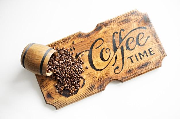 Zerstreute kaffeebohnen auf einem hölzernen brett. Premium Fotos