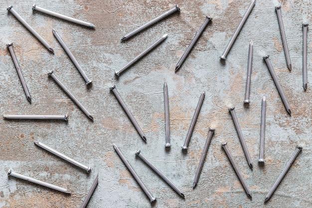 Zerstreute nägel auf hölzernem schreibtisch des schmutzes Kostenlose Fotos