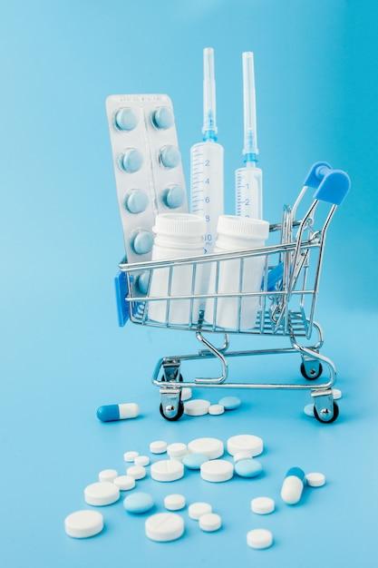 Zerstreute pillen, tabletten und kapseln der pharmazeutischen medizin auf dem dollargeld lokalisiert auf blauem hintergrund. medikamentenkosten. Premium Fotos