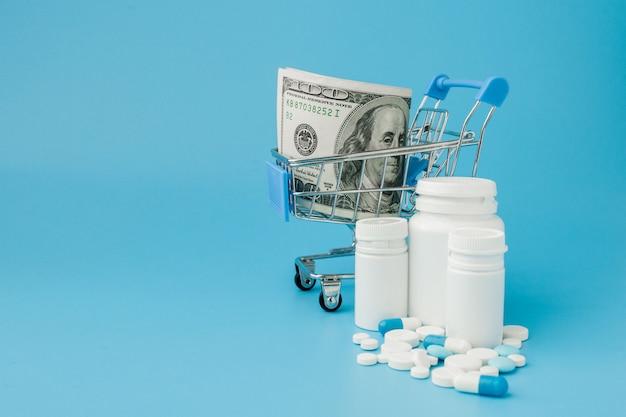 Zerstreute pillen, tabletten und kapseln der pharmazeutischen medizin auf dem dollargeld lokalisiert auf blauem hintergrund Premium Fotos