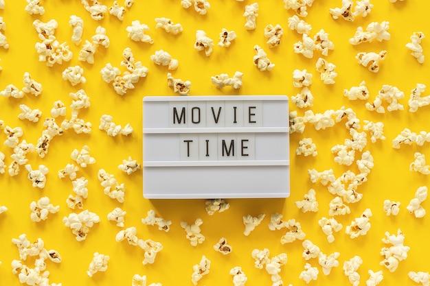 Zerstreute popcorn- und lightbox-text filmzeit auf gelbem papierhintergrund. Premium Fotos