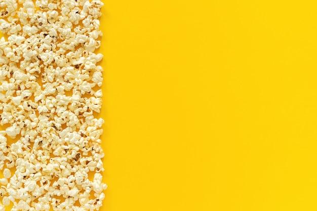 Zerstreuter popcornrand linker rand und leerer raum auf gelbem papierhintergrund. Premium Fotos
