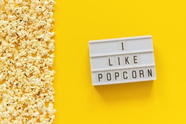 Zerstreuter popcornrand linker rand und leuchtkasten-text mag ich popcorn auf gelbem papierhintergrund. Premium Fotos