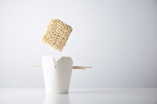 Ziegel aus trockenen nudeln fällt in eine leere imbissschachtel mit essstäbchen, die auf einem weißen kommerziellen einzelhandelsset isoliert sind Kostenlose Fotos