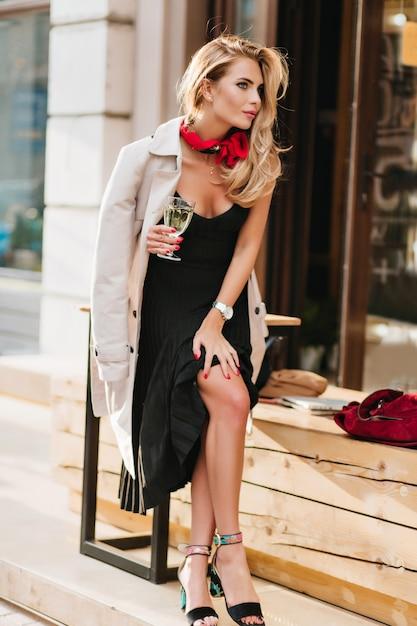Ziemlich gelangweiltes mädchen in schwarzen sandalen, die jemanden warten und champagner nahe restaurant trinken Kostenlose Fotos