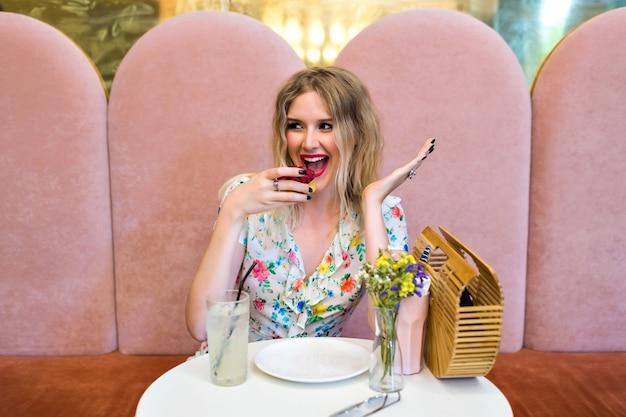 Ziemlich glückliche blonde hipster-frau, die leckeren himbeer-dessertkuchen isst, bei niedlicher bäckerei sitzt, ihr essen, süßes frühstück, diät-ernährungskonzept genießt. Kostenlose Fotos