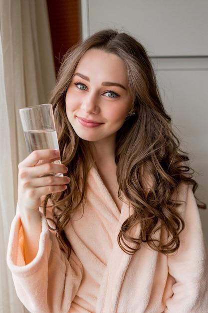 Ziemlich glückliche frau im bademantel, die zu hause frisches wasser trinkt Kostenlose Fotos