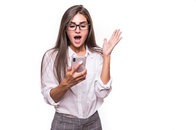 Ziemlich glückliche überraschte dame, die mit handy auf weißer wand aufwirft Kostenlose Fotos