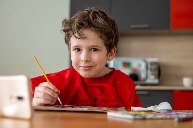 Ziemlich glücklicher kleiner junge, der zu hause mit online-fernunterricht zeichnet Premium Fotos