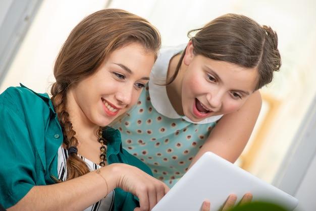 Ziemlich schöne charmante teenager und ihre ältere freundin tabletts Premium Fotos