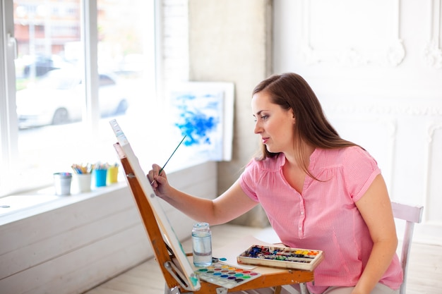Ziemlich talentierte malerin malerei auf staffelei Premium Fotos