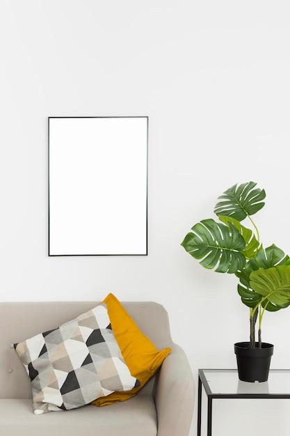 Zierpflanze mit leerem rahmen und sofa Kostenlose Fotos