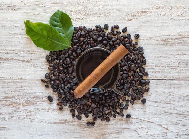 Zigarre auf einer tasse schwarzen kaffee mit kaffeebohnen. Premium Fotos