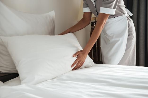 Zimmermädchen macht bett im hotelzimmer Kostenlose Fotos