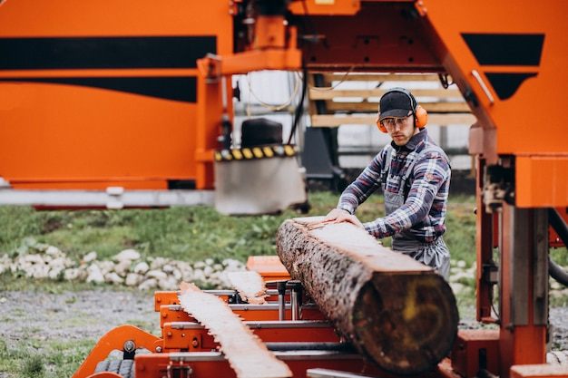 Zimmermann, der an einem sägewerk auf einer holzmanufaktur arbeitet Kostenlose Fotos