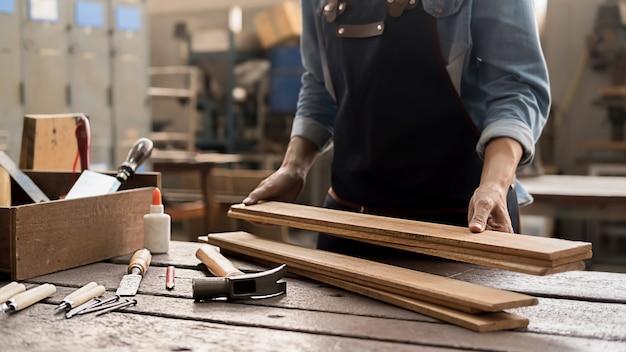 Zimmermann, der mit ausrüstung auf holztisch in der tischlerei arbeitet. frau arbeitet in einer tischlerei. Premium Fotos