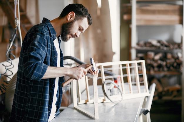 Zimmermann hämmert einen nagel in einer werkstatt Kostenlose Fotos