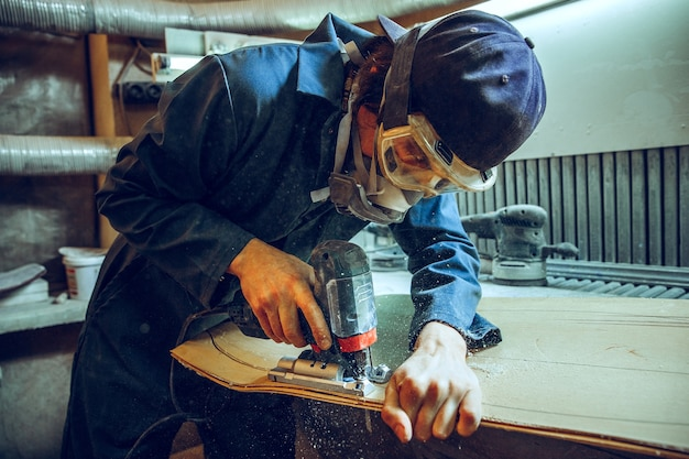 Zimmermann mit kreissäge zum schneiden von holzbrettern. konstruktionsdetails des männlichen arbeiters oder des handlichen mannes mit elektrowerkzeugen Kostenlose Fotos