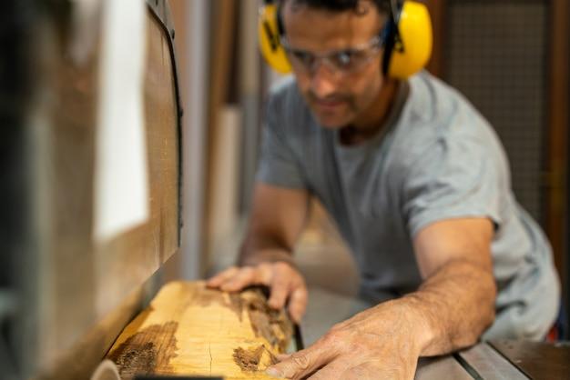 Zimmermann schneidet holz mit einer maschine, die ohrstöpsel trägt. Premium Fotos
