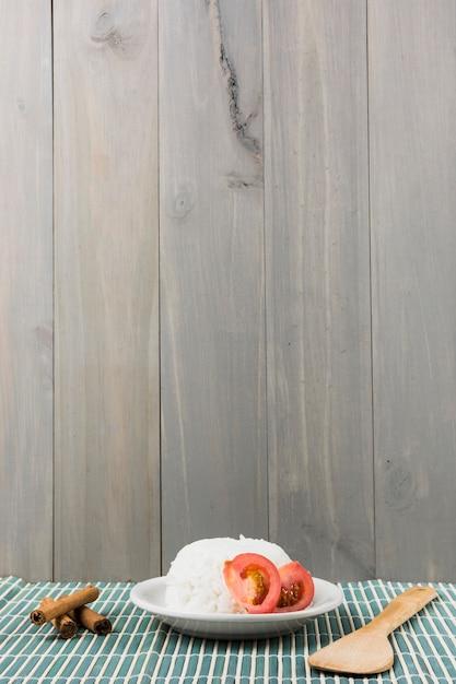 Zimtstangen; spachtel und platte des weißen reises mit tomate schneiden auf tischset gegen hölzernen hintergrund Kostenlose Fotos