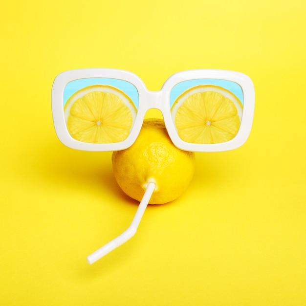 Zitrone in sonnenbrille auf gelb. sommer saftige farbe. Premium Fotos