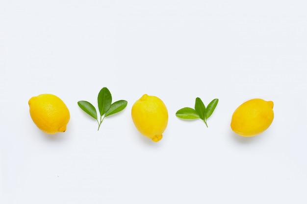 Zitrone und scheiben mit den blättern getrennt auf weiß. Premium Fotos
