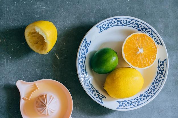 Zitronen, limette, orange in einer weißen keramikplatte mit muster, zitruspresse Premium Fotos