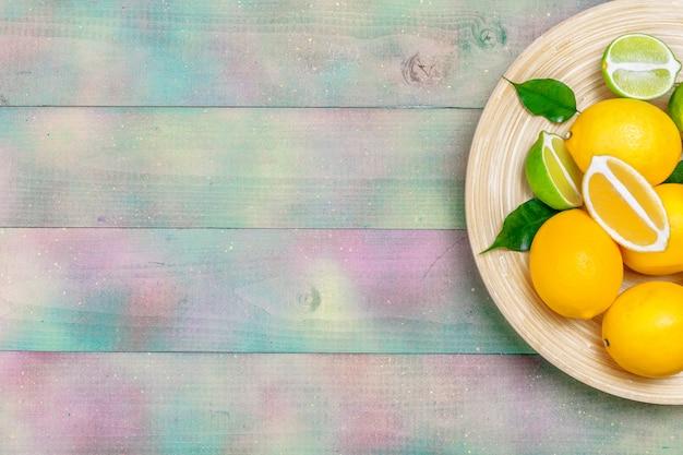 Zitronen und limetten auf einem hölzernen. Premium Fotos