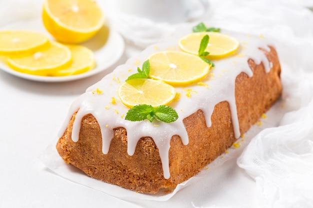 Zitronenkuchen mit zuckerglasur auf einem weißen hintergrund Premium Fotos