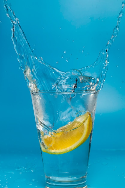 Zitronenscheibe fällt und fällt in ein spritzglas Premium Fotos