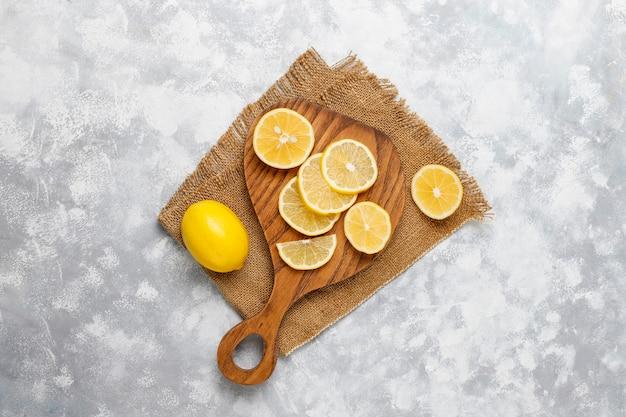 Zitronenscheiben auf schneidebrett auf beton schneiden. draufsicht, kopie, raum Kostenlose Fotos