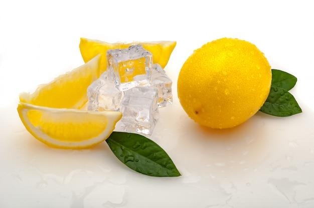 Zitronenscheiben, grüne blätter, kaltes eiswürfel und eine ganze frische gelbe zitrone auf einem weißen hintergrund Premium Fotos