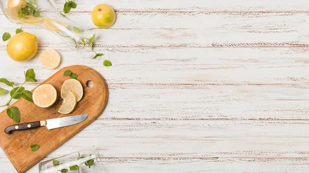 Zitronenscheiben nahe messer zwischen pflanzen und gläsern Kostenlose Fotos