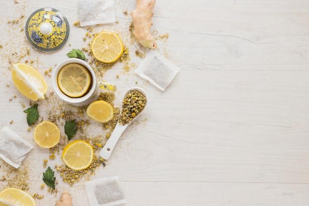 Zitronentee mit getrockneten chinesischen chrysanthemenblumen und zitronenscheiben auf holztisch Kostenlose Fotos