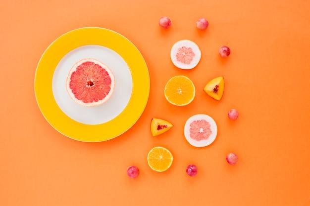 Zitrusfrucht; pfirsichscheiben und trauben auf einem orangefarbenen hintergrund Kostenlose Fotos