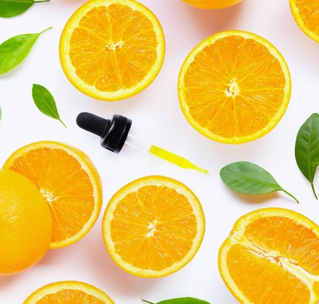 Zitrusfruchtätherisches öl mit der frischen orange frucht getrennt auf weiß Premium Fotos